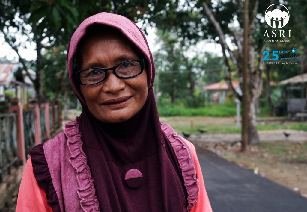 A woman receives a new pair of glasses through ASRI's partnerships with Essilor 2.5 New Vision Generation initiative.