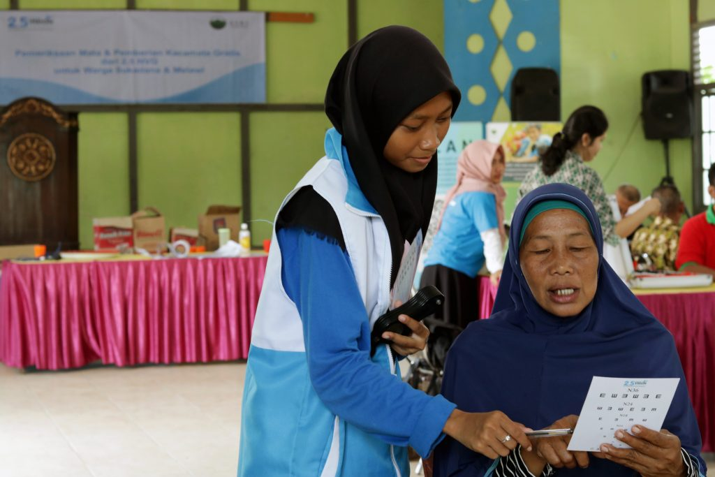 A student from the ASRI teens program helps conduct a basic eye exam at the ASRI Environmental Health Clinic in West Kalimantan, Indonesia.