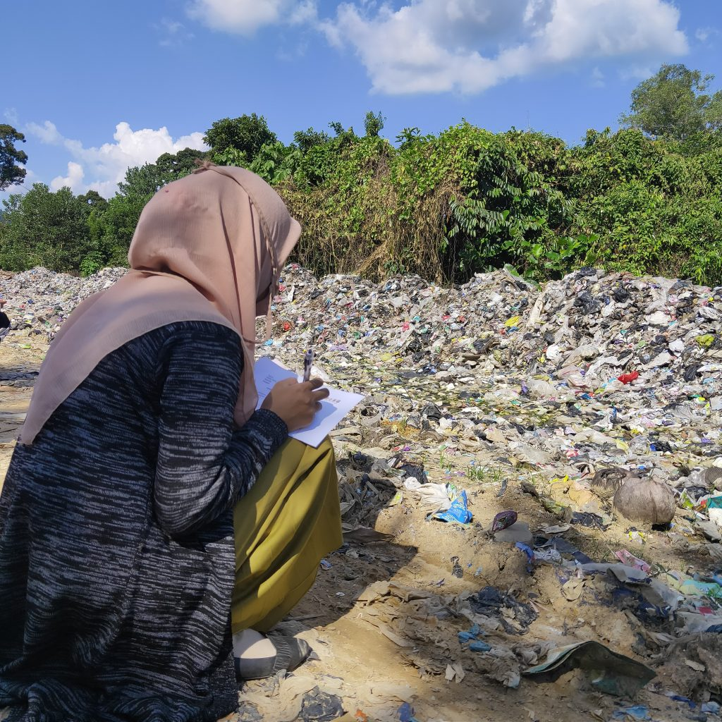 A student writing down her reflections on the landfill and how the waste is polluting the Earth.