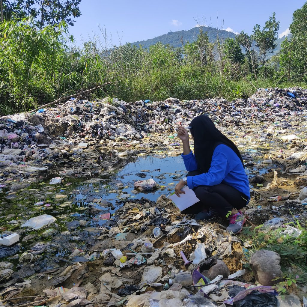 Student observing the effects of waste pollution in the puddles at the landfill.