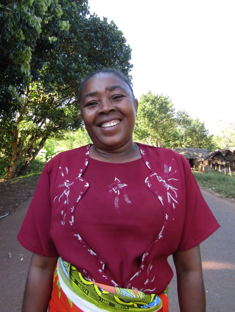 Photo of Nelly Ranjemiarisoa, a new member of the team in Madagascar: a woman dressed in a red shirt with white patterns, and a colorful skirt.